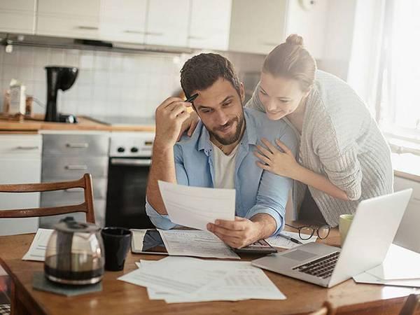 Baufinanzierungsrechner, Baufinanzierung, Paar sitzt am Küchentisch und berechnet gemeinsam ihre Immobilienfinanzierung, Foto: iStock/Geber86