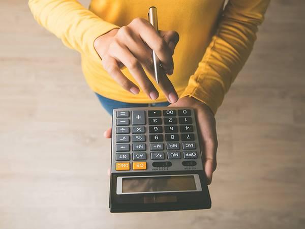 Baukreditrechner, Hypothekenrechner, Zinsrechner, Baukredit, Zinsen, Hände mit Taschenrechner, Foto: iStock.com/Kritchanut