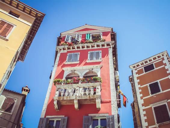 Immobilienkauf Kroatien, Froschperspektive auf die bunten Fassaden schmaler alter Häuser in der Altstadt von Rovinj, Foto: Erik-Jan Leusink / unsplash.com