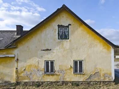 Bauernhaus kaufen, gelbes Haus mit deutlich erkennbarer maroder Substanz, Foto: leopold/stock.adobe.com