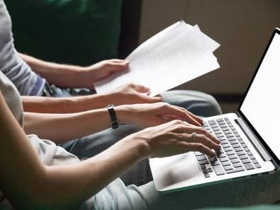 Tilgungsrechner, Eingabe, Frau sitzt mit Laptop auf dem Schoß, ein Mann mit Unterlagen daneben, Foto: fizkes/stock.adobe.com