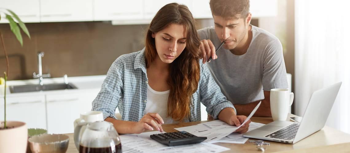 Tilgungsrechner, Paar sitzt am Tisch über Unterlagen und rechnet mit dem Taschenrechner, Foto: Wayhome Studio/stock.adobe.com