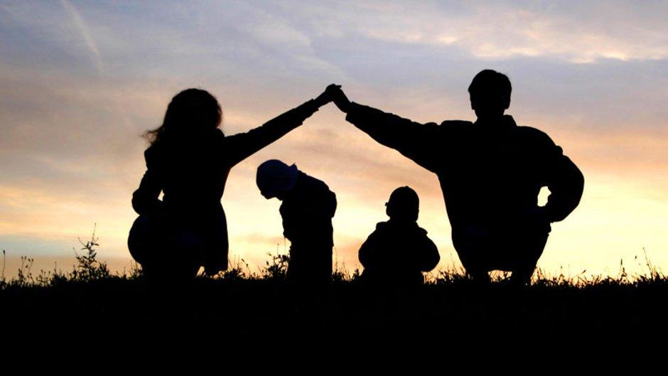 Wohnraumförderungsgesetz, eine Familie, die Eltern bilden mit den Armen ein Dach über den Kopf ihrer beiden Kinder, Foto: Pavel-Losevsky / stock.adobe.com