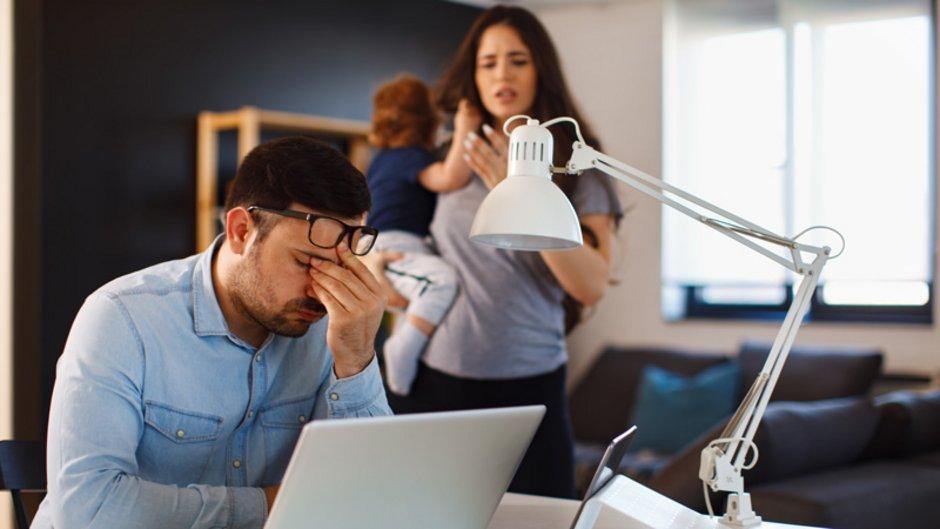 Restschuldversicherung, Mann sitzt verzweifelt vor dem Laptop und wird von Frau im Hintergrund mit Kind auf dem Arm beobachtet, Foto: djile / stock.adobe.com