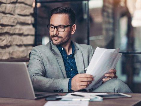 Ein Mann am Arbeitsplatz mit Laptop und Papier.