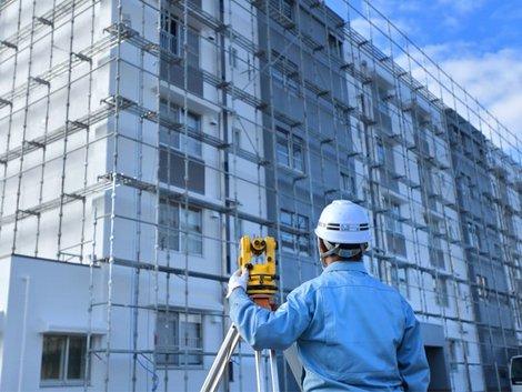 Liegenschaftskataster, Vermessungsingenieur misst Gebäude von außen ein, Foto: godfather/stock.adobe.com