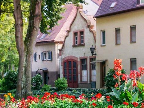 Kauvvertrag, Altbauten mit Blumen und Bäumen im Vordergrund, Foto: iStock / TomekD76