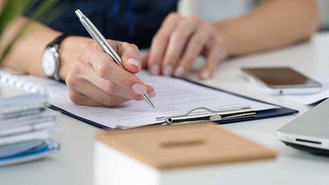 Mieterselbstauskunft, Selbstauskunft, Hände mit Stift füllen einen Zettel auf einem Klemmbrett aus, Foto: iStock.com / Dutko