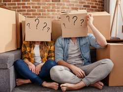 Corona, Umzug, Paar sitzt auf dem Boden und hat Kartons auf dem Kopf auf die Fragezeichen gemalt sind, Foto: alphaspirit / stock.adobe.com