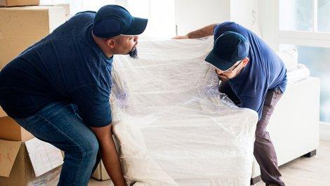 Helfer tragen einen verpackten Sessel: Foto: iStock.com / Rawpixel
