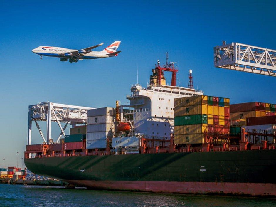 Auswandern Australien, Ein Containerschiff liegt in einem Hafen vor Anker, Foto: unsplash.com/vanveenjf