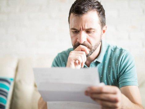 Zweitwohnsitzsteuer, Mann prüft Brief mit besorgtem Gesichtsausdruck, Foto: AntonioDiaz/ stock.adobe.com