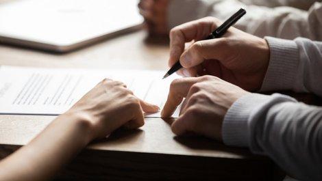 Fallen im Mietvertrag, ein Mann unterschreibt ein Dokument an der Stelle, auf die eine Frau deutet, Foto: fizkes / stock.adobe.com