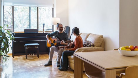 Homeoffice steuerlich absetzen, Gitarrenlehrer mit Schülerin auf dem Sofa bei Gitarrenunterricht, Foto: beavera / stock.adobe.com