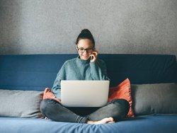 Homeoffice steuerlich absetzen, Frau sitzt auf Sofa mit Laptop auf dem Schoß und Handy am Ohr, Foto: franz12 / stock.adobe.com