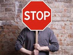 Diskriminierung auf dem Wohnungsmarkt, Mann hält sich ein Stop-Schild vor sein Gesicht, Foto: papa/stock.adobe.com