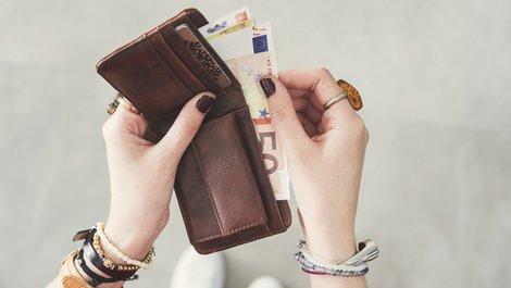 Fallen im Mietvertrag, eine Frau holt einen 50-Euro-Schein aus einem Portemonnaie, Foto: sebra / stock.adobe.com