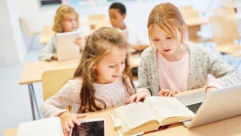Stadtflucht, Grundschüler lernen mit Buch und Laptop, Foto: Robert Kneschke / stock.adobe.com