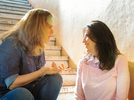 Diskriminierung auf dem Wohnungsmarkt, zwei Frauen sitzen im Treppenhaus und unterhalten sich, Foto: iStock.com/NicolasMcComber