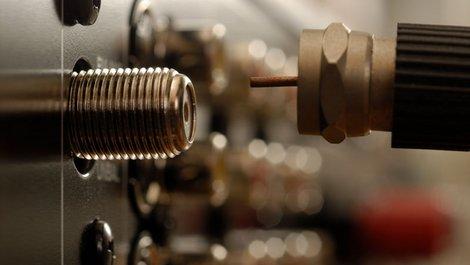 Ein Sat-Kabel wird aus de Buchse gezogen, Foto: istock.com / KLH49