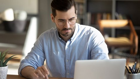 Instandhaltungsrücklage, ein Foto von einem Mann mit Brille, der vor einem Laptop sitzt und auf einen Taschenrechner tippt, Foto: fizkes / stock.adobe.com