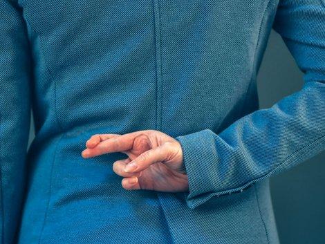 Hinter dem Rücken gekreuzte Finger