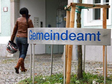 Zweitwohnsitzsteuer, dunkelhaarige Frau geht in das Gemeindeamt, Foto: Gina Sanders/stock.adobe.com