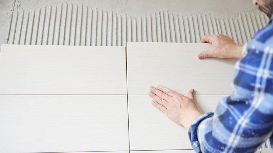 Wann Mietern eine Renovierung zusteht, Mann fliest eine Wand neu, Foto: CreativePhotography / stock.adobe.com