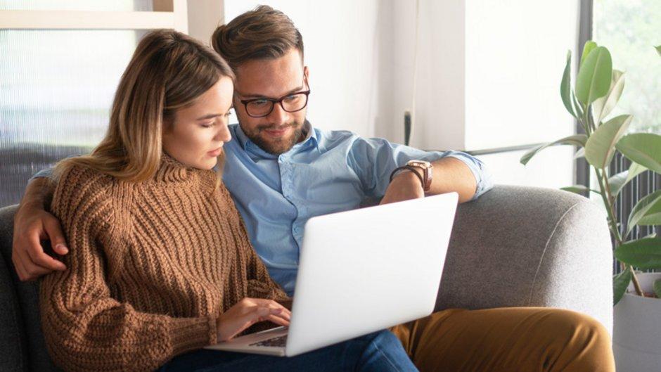 Tipps zur Wohnungssuche, Paar sitzt mit Laptop auf dem Sofa und sucht eine Wohnung, Foto: Stock Rocket / stock.adobe.com