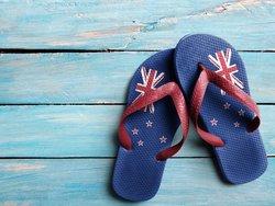 Auswandern nach Neuseeland, Ein Paar Flipflops mit dem Aufdruck der Flagge von Neuseeland liegt auf Holz, Foto: zerophoto/stock.adobe.com