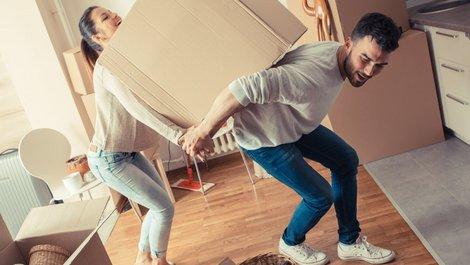 Umzugskartons packen, Paar schleppt gemeinsam Umzugskarton, Umzugskarton zu schwer, Foto: BalanceFormCreative / stock.adobe.com