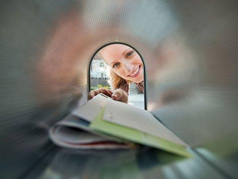 Eine Frau greift nach Briefen in einem Briefkasten