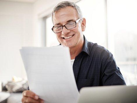Miete mindern, Miete kürzen, Mietminderung widersprechen, Vermieter, ein Mann liest ein Dokument und lächelt, Foto: iStock.com/Tinpixels