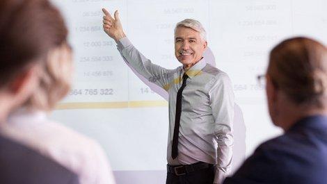 Instandhaltungsrücklage, Foto von einem Mann mit Hemd und Krawatte, der vor einer Präsentation mit Zahlen steht, im Vordergrund sieht man verschwommen die Zuschauer, Foto: iStock.com / MangoStar Studio
