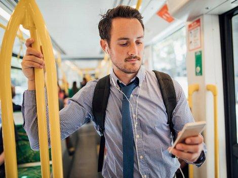 Auswandern Australien, ein Mann sucht auf seinem Handy nach einem Job, Foto: iStock.com/DGLimages