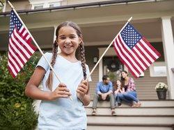 Auswandern in die USA, Mädchen im Vordergrund hält zwei USA-Flaggen in der Hand; im Hintergrund: Familie sitzt auf den Stufen eines Hauses, Foto: Monkey Business/stock.adobe.com