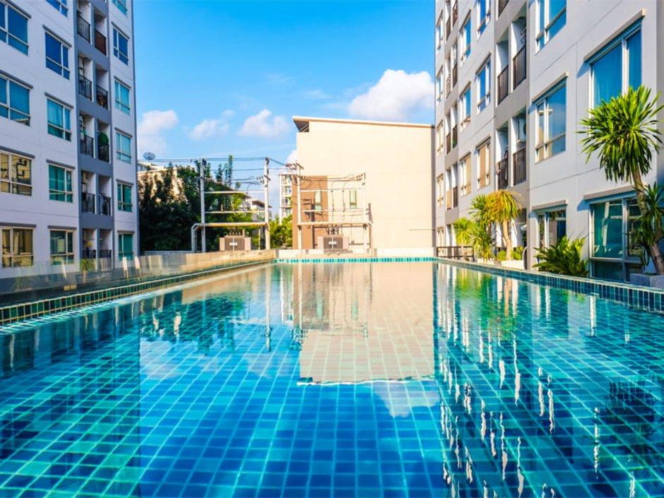 Auswandern nach Thailand, Wohnungen in zwei sich gegenüberstehenden Gebäudekomplexen. In der Mitte ist ein Pool, Foto: themorningglory/stock.adobe.com