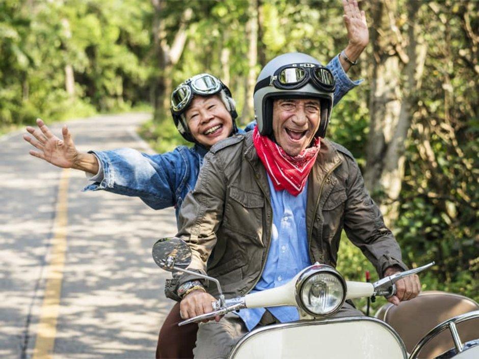 Auswandern nach Thailand, zwei lachende Rentner auf einem Motorroller fahren eine Straße entlang, Foto: Rawpixel.com/stock.adobe.com