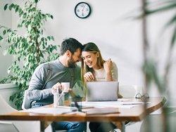 Wohn-Riester, Bild von einem glücklichen Pärchen vor einem Laptop und vielen Unterlagen auf dem Tisch ausgebreitet, Foto: picsfive / stock.adobe.com