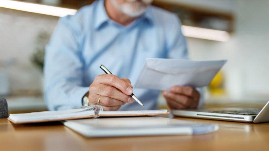 Mietrückstand: Ein Mann am Schreibtisch, in der Hand einen Briefumschlag und einen Stift, Foto: istock.com / nortonrsx