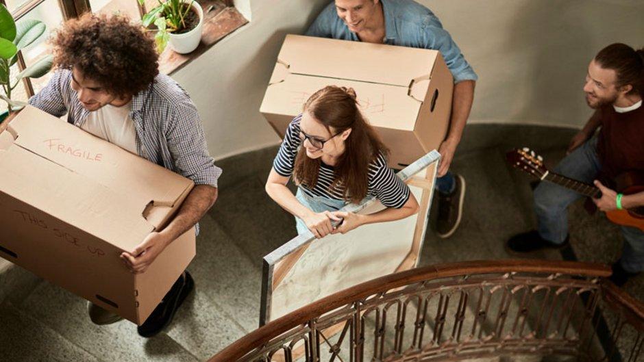 Helfer im Treppenhaus mit Umzugskisten. Foto: iStock.com / Geber86