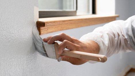 Eine Person trägt mit dem Pinsel unterhalb des Fensters Farbe auf. Foto: istock.com / Bill Oxford