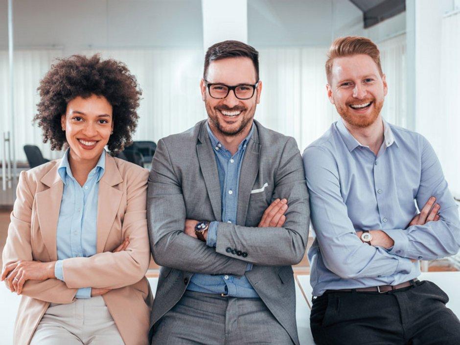 Makler, Käufer und Verkäufer lehnen sich gemeinsam an eine Tischkante und lachen.