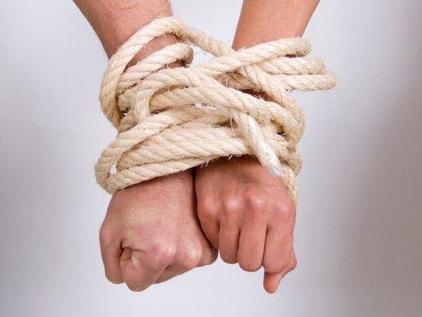 Immobilie geerbt, Erbengemeinschaft, Frau und Mann sind mit einem Seil an den Handgelenken gefesselt, Foto: iStock/Cirilopoeta