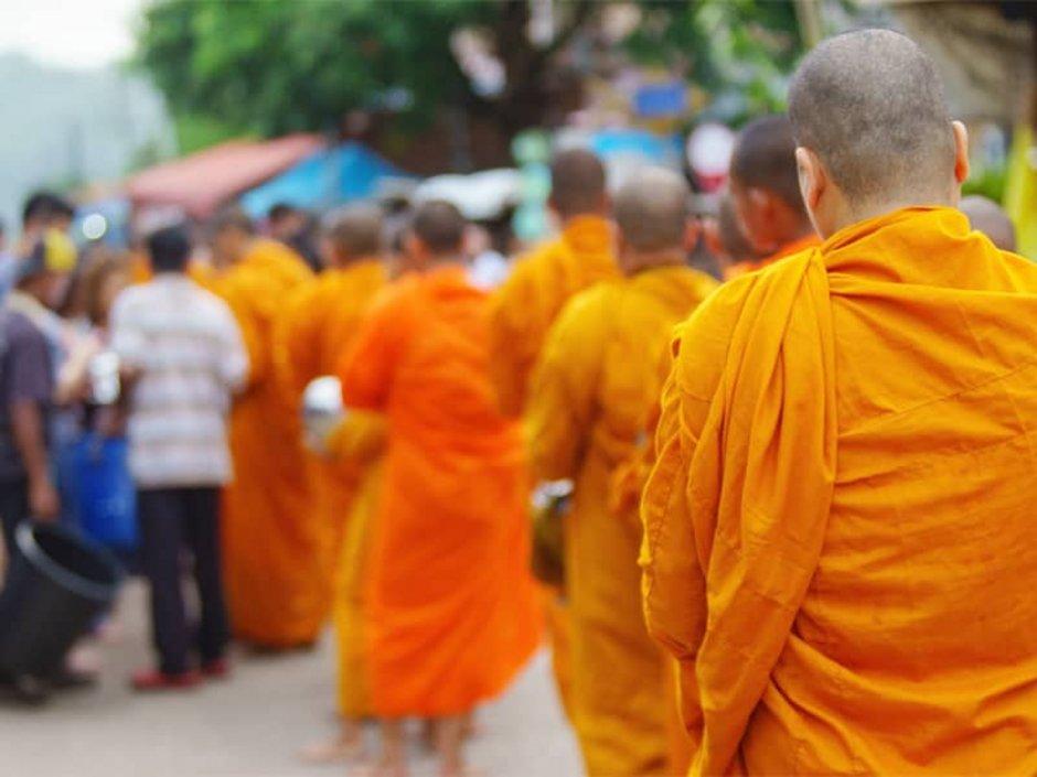 Auswandern nach Thailand, buddhistische Mönche laufen hintereinander durch eine Menschenmenge, Foto: workingascene/stock.adobe.com