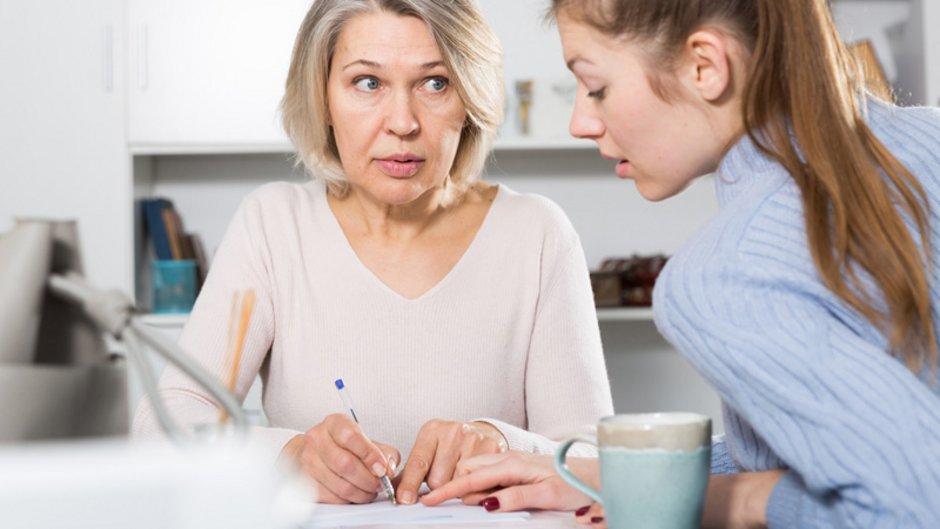 Mietbürgschaft, ältere Frau unterschreibt ein Dokument an einer Stelle, die von einer jungen Frau gezeigt wird, Foto: JackF / stock.adobe.com