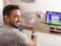 Rundfunkbeitrag, Mann mit Fernbedienung in der Hand sieht fern, Foto: sakkmesterke / stock.adobe.com