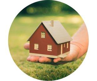 Bausparen, Baufinanzierung, Immobilie sofort finanzieren, eine Hand hält ein Modellhaus vor einer Wiese, Foto: Fokussiert/stock.adobe.com