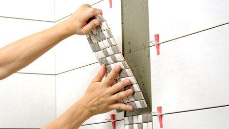 Eine Person klebt eine Fliese an die Wand. Foto: gpmax / stock.adobe.com