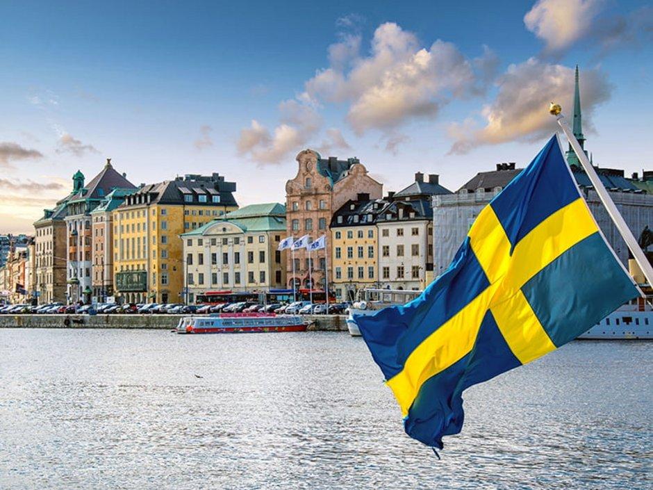 Auswandern nach Schweden, Schwedische Fahne im Vordergrund, Hafen von Stockholm im Hintergrund Foto: AlexiTauzin/stock.adobe.com